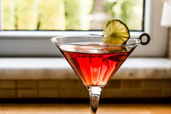 Cosmopolitan Cocktail with lime on wooden surface. Stock Photography