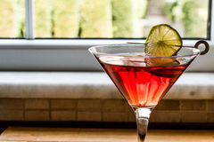 Cosmopolitan Cocktail with lime on wooden surface. Royalty Free Stock Photography