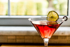 Cosmopolitan Cocktail with lime on wooden surface. Royalty Free Stock Photos