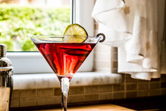 Cosmopolitan Cocktail with shaker on wooden surface. Royalty Free Stock Images