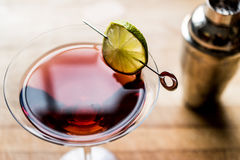Cosmopolitan Cocktail with shaker on wooden surface. Beverage Concept royalty free stock photos