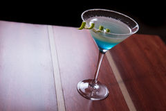 Cosmopolitan drink. A refreshing blue drink decorated with a spiral lime stock photo