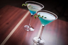 Cosmopolitan drink. A refreshing blue drink decorated with a spiral lime royalty free stock image