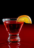 Cosmopolitan Martini. A cosmo martini with an orange slice with a red and black background Stock Image