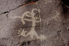 Coso Range Petroglyph. Native American rock art petroglyph close up of anthropomorphic like figure shooting a bow and arrow carved into desert varnish and lichen Royalty Free Stock Images