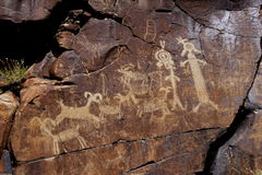 Coso Range Petroglyphs. Native American rock art petroglyphs of various sheep and anthropomorphic like figures carved into desert varnish covered cliffs in Royalty Free Stock Image