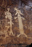 Coso Range Petroglyphs. Native American rock art petroglyph close up of two anthropomorphic like figures carved into desert varnish covered cliff in Little Stock Photo