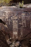 Coso Range Petroglyphs. Native American rock art petroglyph close up of several anthropomorphic like figures carved into desert varnish covered rock in Little Royalty Free Stock Photos