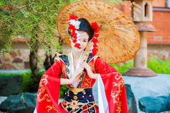 Cosplay. beautiful, modest geisha in a red kimono. Posing with umbrella Royalty Free Stock Photos