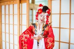 Cosplay bella, geisha modesta in un kimono rosso Fotografia Stock
