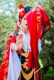 Cosplay bella, geisha modesta in un kimono rosso Immagine Stock