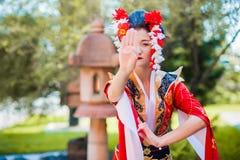 Cosplay bella, geisha modesta in un kimono rosso Fotografia Stock Libera da Diritti