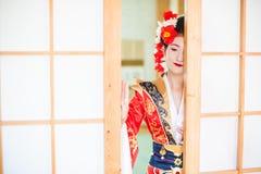 Cosplay bella, geisha modesta in un kimono rosso Fotografie Stock
