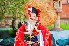 Cosplay bella, geisha modesta in un kimono rosso Fotografie Stock Libere da Diritti