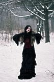 Cosplay black witch in winter forest Stock Photo