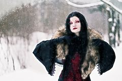 Cosplay black witch in winter forest Royalty Free Stock Photo