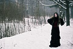 Cosplay black witch in winter forest Stock Photos