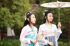 Cosplay Chinese best close friends bestie in traditional ancient drama costume hanfu. Chinese beauty in traditional ancient costume, hold a fan on hand, elegant royalty free stock photography