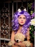 Cosplay flicka i purpurfärgad peruk med den mjuka leksaken arkivfoto
