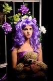 Cosplay flicka i purpurfärgad peruk med leksaken och blommor fotografering för bildbyråer