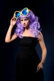 Cosplay flicka i purpurfärgad peruk med stor solglasögon royaltyfri fotografi