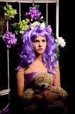 Cosplay girl in purple wig with toy and flowers Stock Image