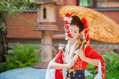 Cosplay härlig blygsam geisha i en röd kimono royaltyfria foton