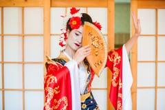Cosplay schöne, bescheidene Geisha in einem roten Kimono Stockbilder