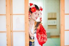 Cosplay schöne, bescheidene Geisha in einem roten Kimono Lizenzfreie Stockbilder