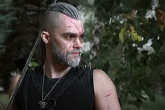 Cosplay, vestido como un héroe Geralt de Rivia del juego el Witcher, un guerrero fantástico con una espada en sus manos Fotografía de archivo libre de regalías