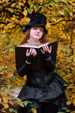 Cosplayer with a book in the autumn park Royalty Free Stock Photo