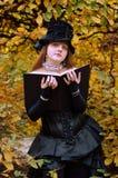 Cosplayer con un libro en el parque del otoño Foto de archivo libre de regalías