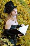 Cosplayer con un libro en el parque del otoño Foto de archivo
