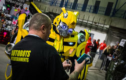 Cosplayer dressed as `Bumblebee` being shown his photo. Sheffield, UK - June 12, 2016:  Cosplayer dressed as `Bumblebee` from `Transformers` being shown his Royalty Free Stock Photos