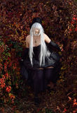 Cosplayer dressed as an undertaker in the autumn park. A teenage girl is wearing a cosplay costume of the undertaker. She is surrounded with the dark reddish Royalty Free Stock Images
