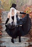 Cosplayer dressed as an undertaker. A teenage girl is wearing a cosplay costume of the undertaker. She is posing on the stone stairs in the autumn park Royalty Free Stock Photo