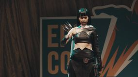 Cosplayer girl showing archer character costume on scene at festival stock footage