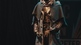 Cosplayer man showing bloodborne character costume on scene at festival. Cosplayer man showing bloodborne video game character costume on scene at festival in stock video