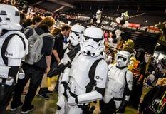 Cosplayers kleidete an, wie Stormtroopers und ein Radfahrer vom Stern kundschaften stockbild