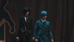 Cosplayers que muestra a animado caracteres con clase trajes en etapa en el festival almacen de metraje de vídeo