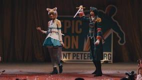 Cosplayers que muestra a caracteres del animado los trajes en etapa en el festival metrajes