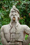 Cossack made of wood. With a forelock and mustache on a background of green leaves Stock Images