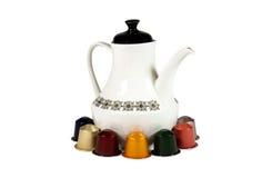 Cosses et pot colorés d'isolement de café sur le blanc Image stock