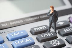 Cost. Think about cost concept. Business figurine stand on calculator near cost button Stock Photo