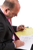 Cost analysis. Businessman making a wage cost analyis (numbers and text on sheets is actual costanalysis, no brandnames are seen Royalty Free Stock Images