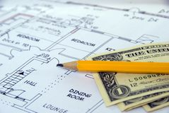 The cost of Building. Dollar bills on building plans, and pencil Royalty Free Stock Photography