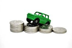 The cost of the car. Car unknown make, situated on stacks of coins stock photo