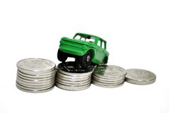 The cost of the car. Car unknown make, situated on stacks of coins royalty free stock photo