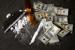 Cost of Cocaine. Powdered cocaine prepared in a line with razor blade and  hundred and twenty dollar bills Stock Image