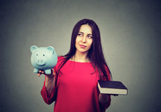 Cost of college education. Thoughtful woman balancing piggy bank and book. Cost of college education. Perplexed thoughtful woman balancing piggy bank in one hand Royalty Free Stock Images